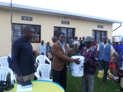 The Project manager - Fulgence Mpayimana handing over a filter to the beneficiaries.